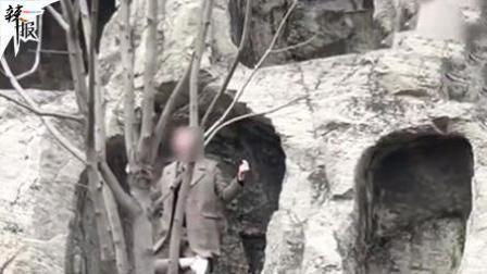 游客爬到龙门石窟洞内搔首拍照