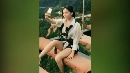 长腿美女高空中淡定自拍 手机不慎摔下山一脸懵