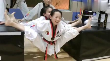 练习跆拳道的孩子腿都压成这样了,居然笑得这么开心,真搞不懂!