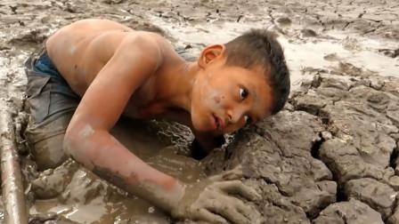 小男孩在土�K里一�D�y掏,�@么干旱的河床,看看他�l�F了什么